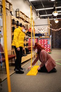 Nancy Cooper of Chelsea, gets help finding some boots from 10-year employee Carly LaForest at Mast Shoe Store in Ann Arbor. The store uses many safety protocols including screens, masks, sanitizing and marked off social distancing areas.